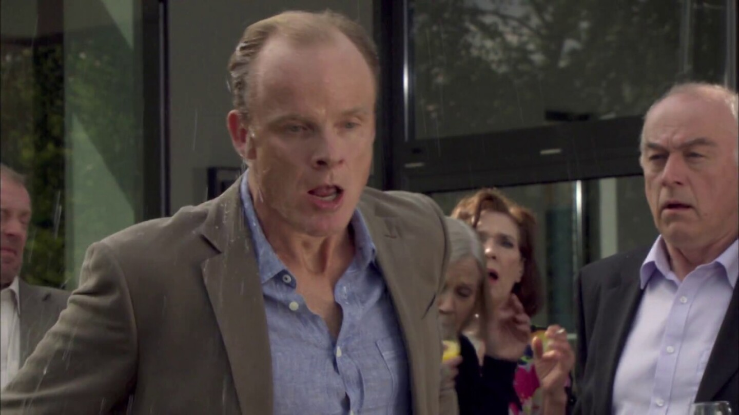 Scene from Midsomer Murders: man walking away from two other men and a women