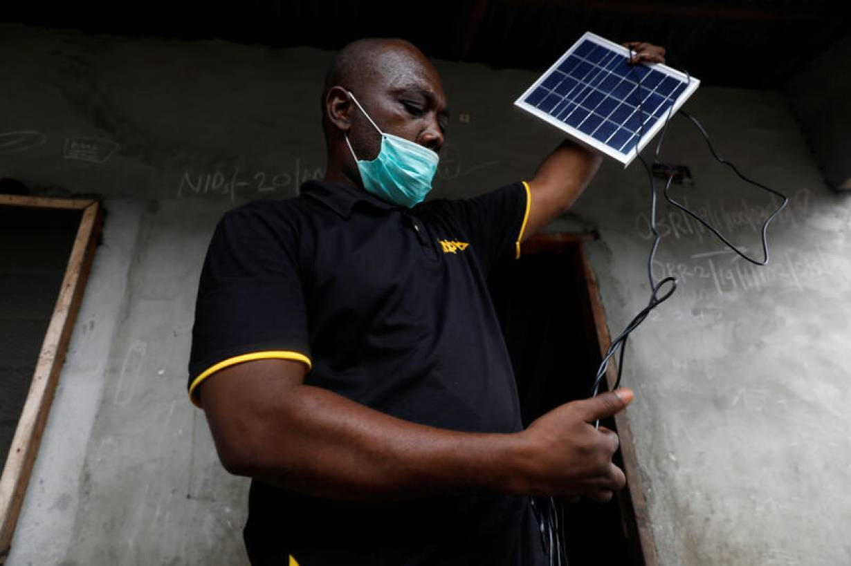 An employee of Salpha Energy unboxes a solar panel for home installation in Sagbo-Kodji community, amid concerns over the spread of coronavirus disease (COVID-19) in Lagos, Nigeria April 25, 2020. | REUTERS/Temilade Adelaja