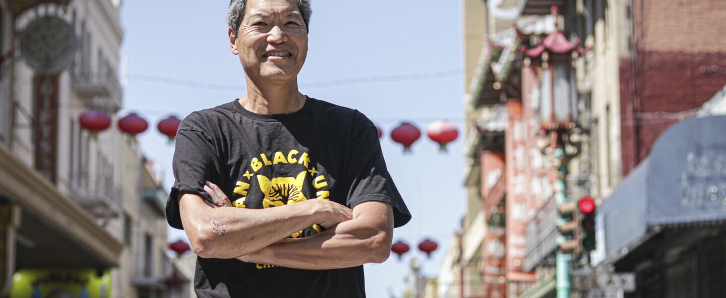 A wrinkled Asian American man in a black t-shirt grins as he crosses his arms across his chest. He stands in Chinatown, San Francisco.