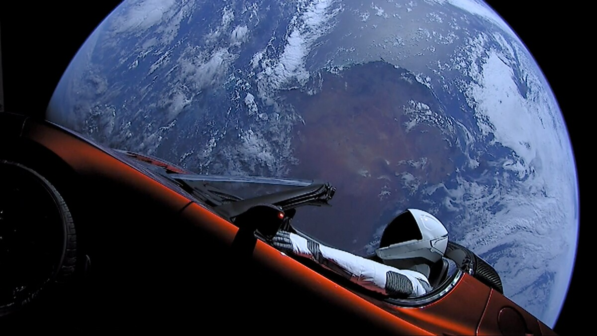 """Elon Musk's Tesla Roadster, with Earth in background. """"Spaceman"""" mannequin wearing SpaceX Spacesuit in driving seat. 