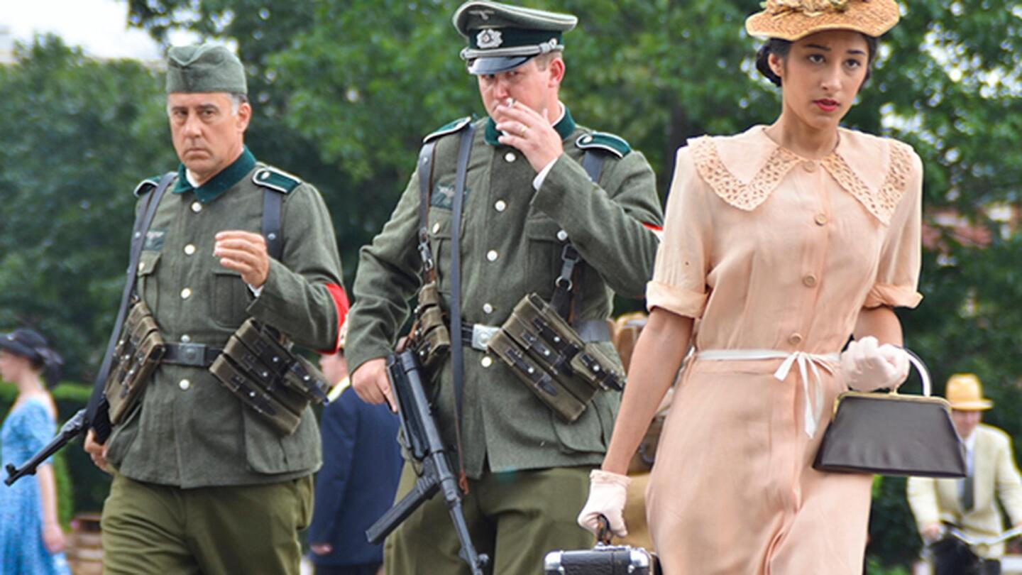 Military officials glance over at a woman walking by dressed in light coral.