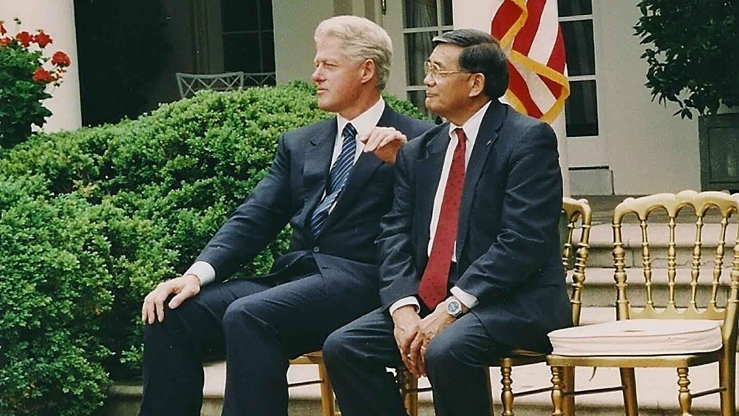 "Norman Mineta sits with President Bill Clinton, who has his hand rested on Mineta's shoulder. | From ""Norman Mineta and His Legacy: An American Story"""