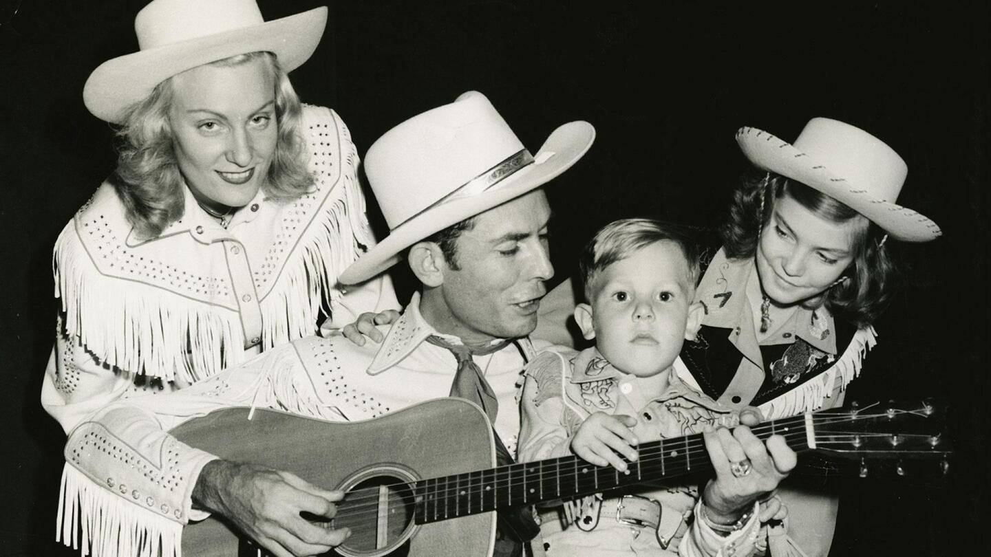 "Hank Williams holds a guitar with a child placing a hand on the frets and a girl behind him, and a woman looks smugly into the camera. | From ""Country Music: The Hillbilly Shakespeare (1945-1953)"""