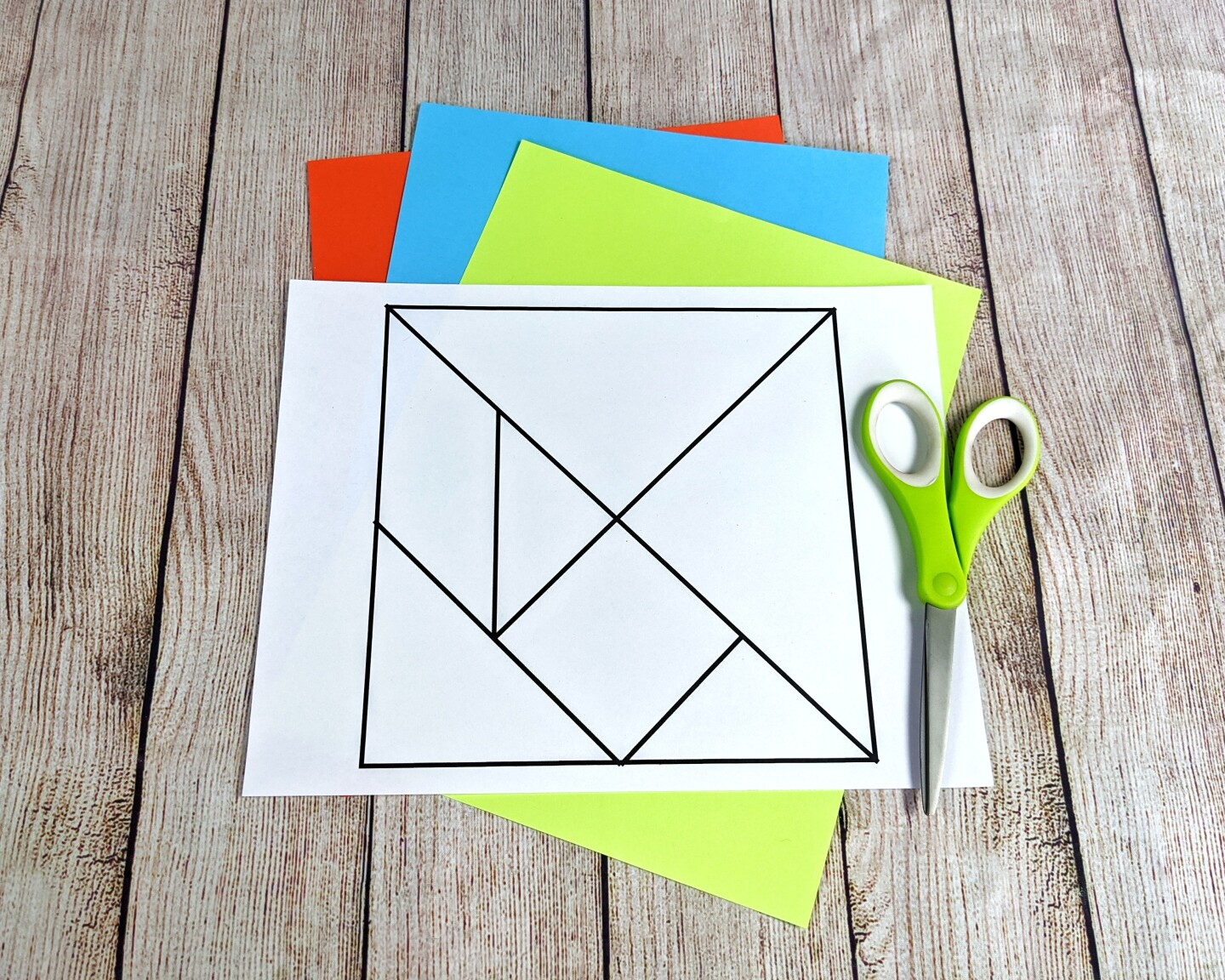 A template for a tangram is laid out on a table alongside some scissors and colorful paper.