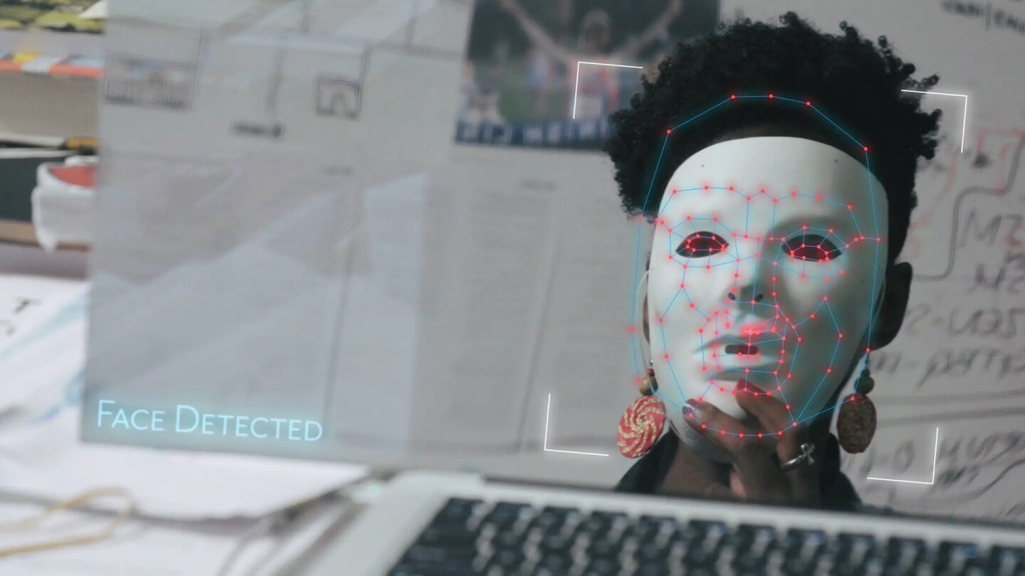 A woman wears a white mask over her face as AI technology scans the mask.