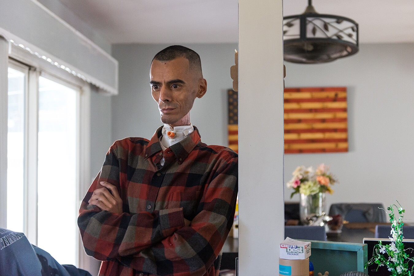 Brian, Rhianna's father, leans against a post in their home. He's standing with his arms crossed, wearing a red button up shirt. Behind him is an American flag wall piece.