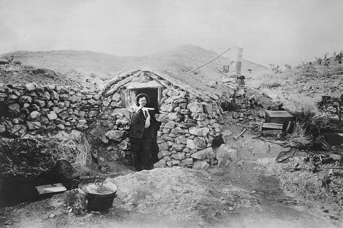 Photograph of an unknown miner at his stone dugout near Randsburg, CA, ca. 1900 -1920. | Courtesy of USC Libraries and California Historical Society.