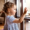 A small child looks at their reflection on a window.