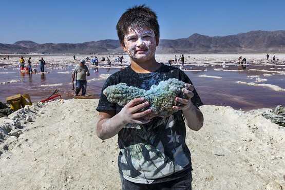 A young boy with a bluish tinged halite specimen.