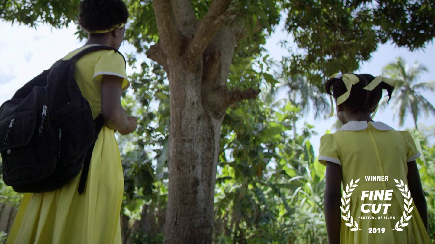 "Two young African girls in yellow uniforms look up at a tree | Still from ""Lalo's House"" Fine Cut 2019"