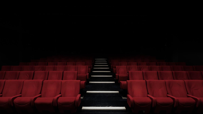 Empty red velvet chairs | Felix Mooneeram / Unsplash