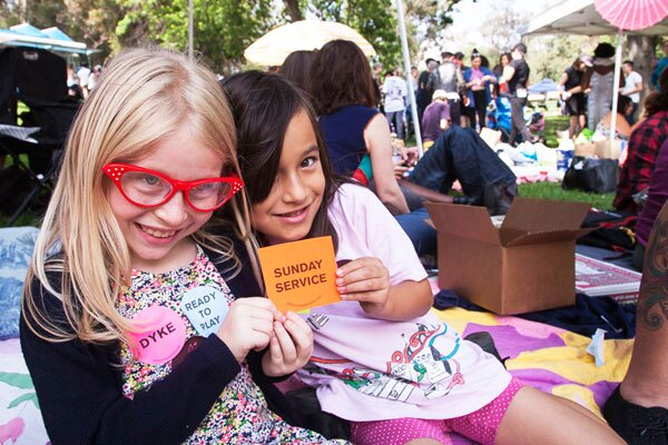 Kids giving away free stickers from Sunday Service at Dyke Day | Photo: Maya Santos