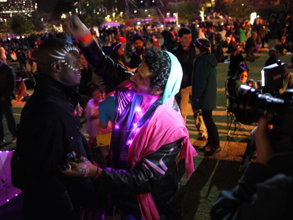 New Year's Eve revelers paint one another with glow in the dark paint