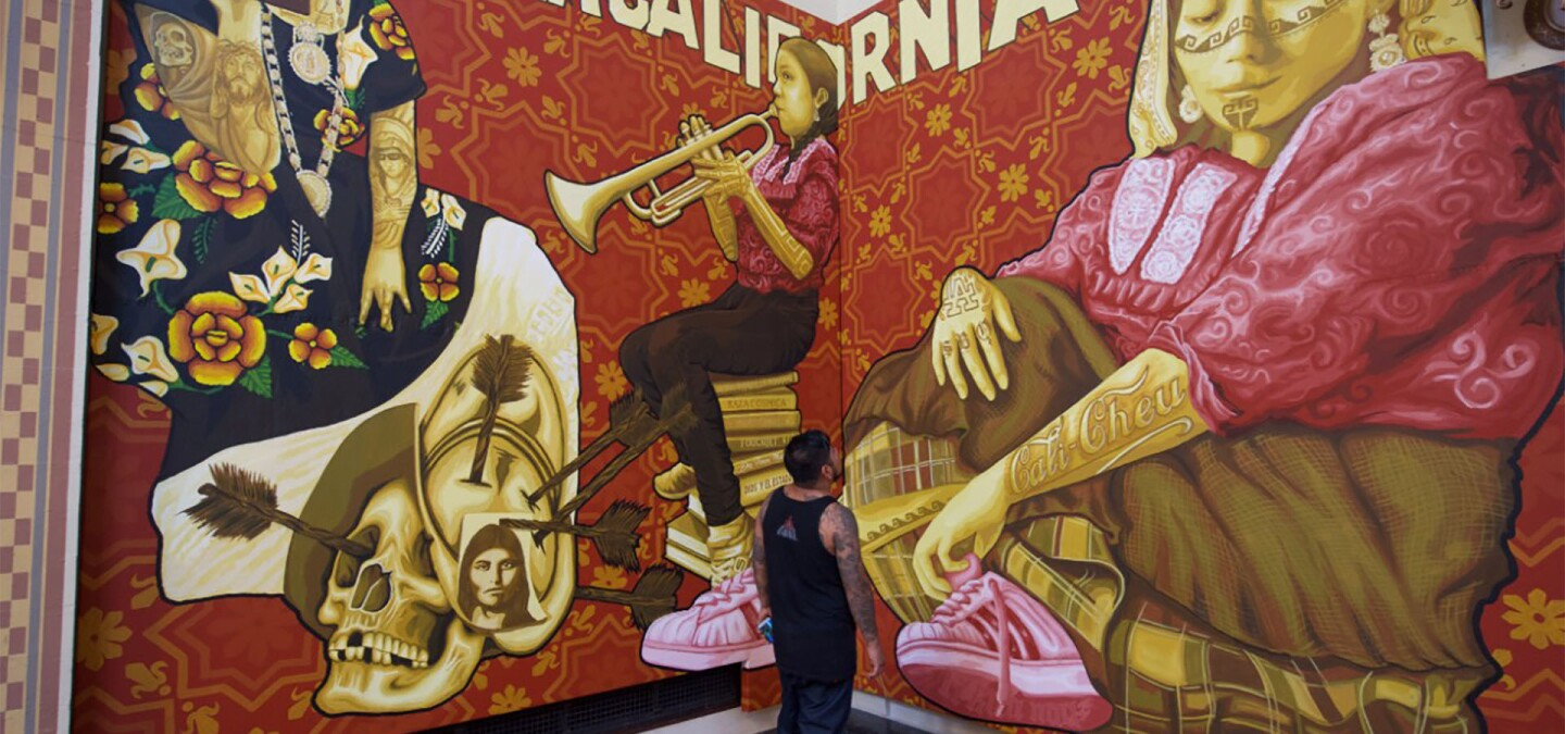 Dario Canul of artist collective Tlacolulokos stands in front of mural that depicts the two sides of Oaxaca | Gary Leonard