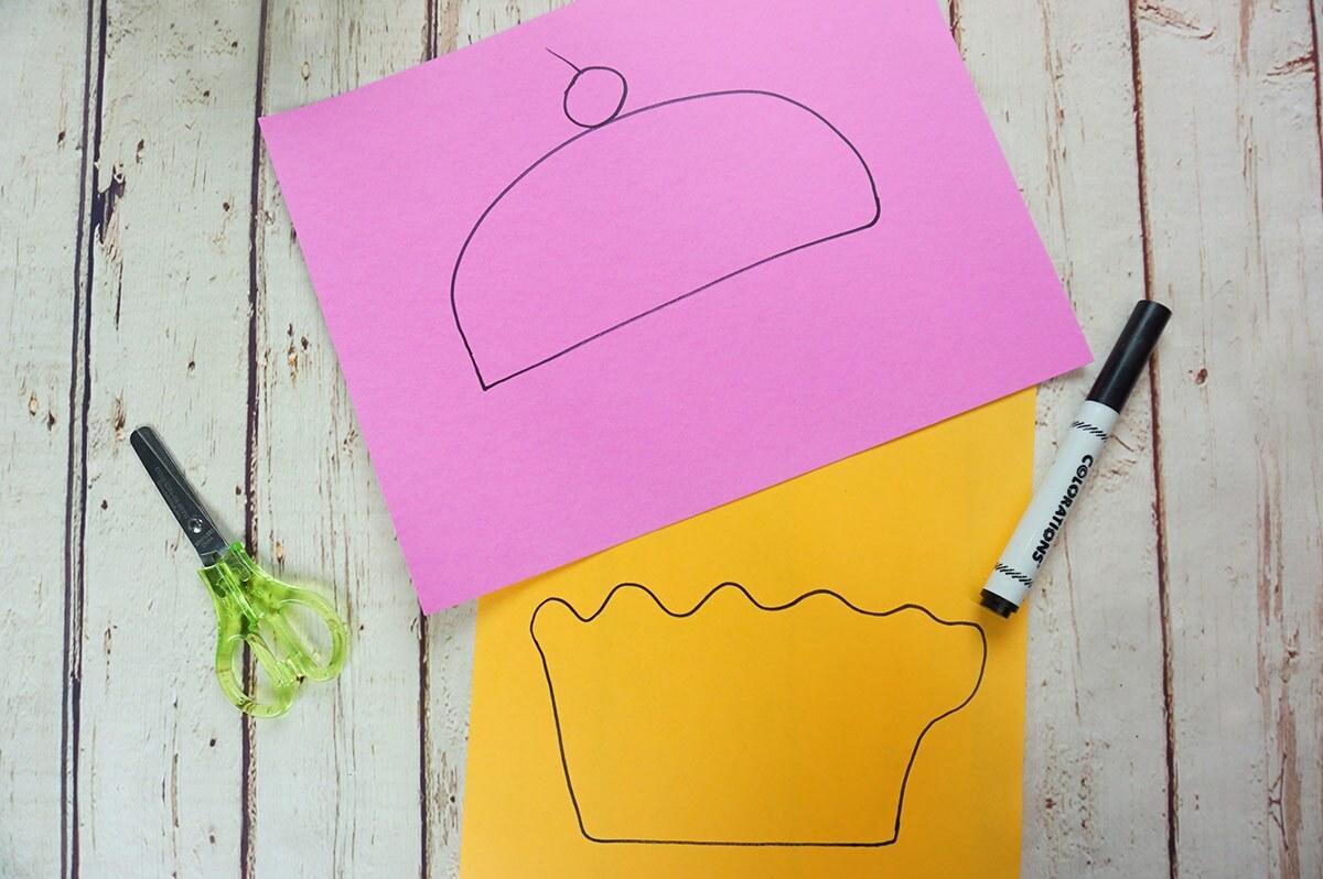 Dos hojas de papel, una rosa y otra naranja, con la partes superior e inferior de un pastelido dibujada sobre ellas.