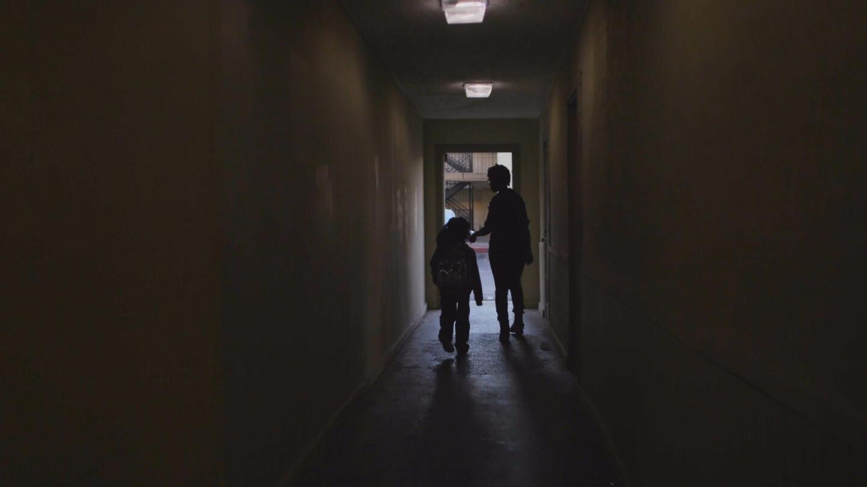 A child and a woman walk through a dark hallway.