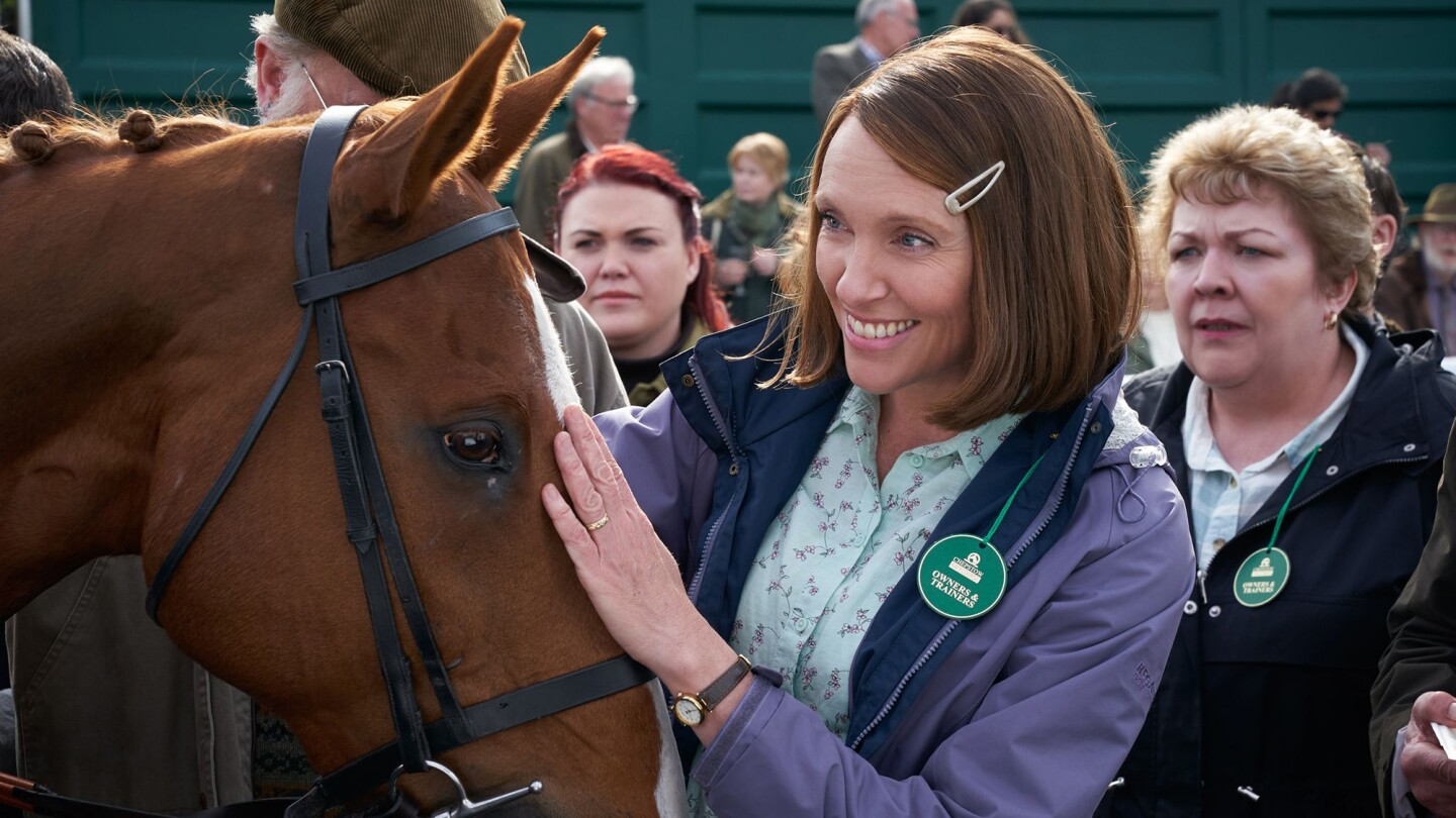 Toni Collette as Jan Vokes smiles and places her hand on a horse.