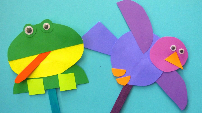 Un par de marionetas en forma de de rana y pájaro sobre un fondo azu