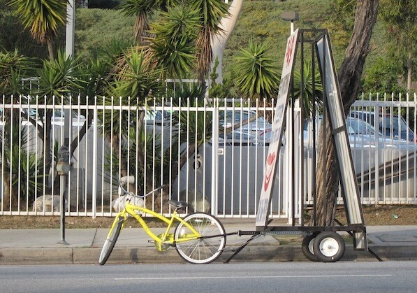 A mobile billboard attached to a bicycle was seen Sunday in the Cahuenga Pass | Photo by Zach Behrens/LAist