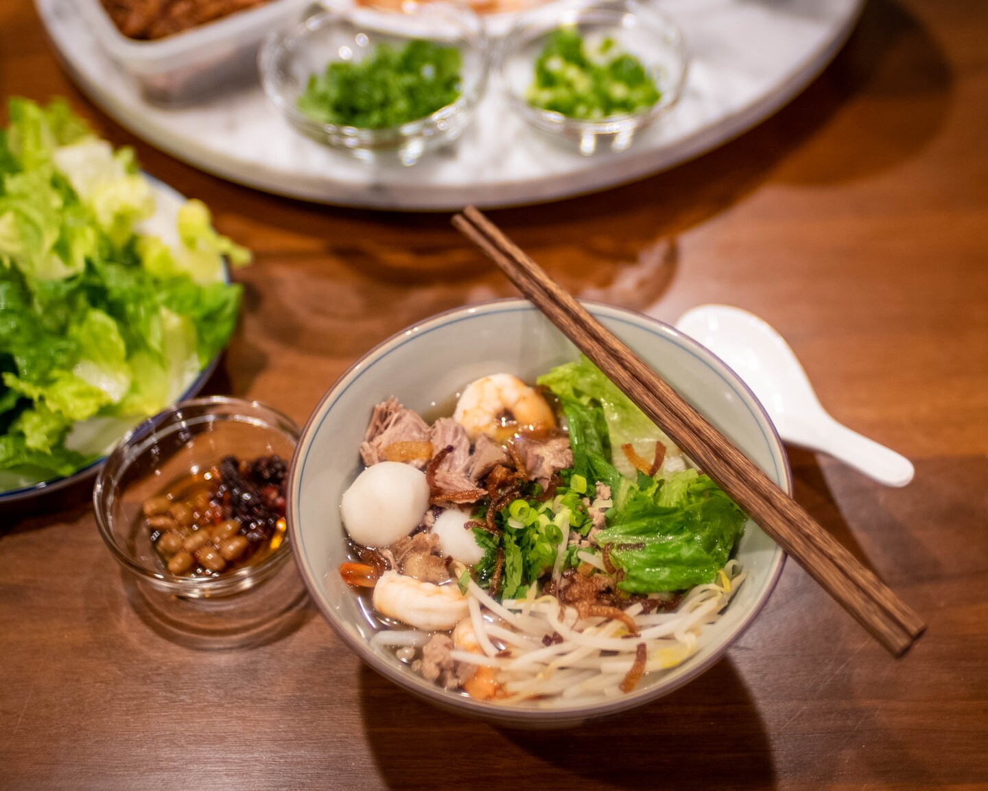 A bowl of Teochew noodles served with pork and seafood in broth garnished with fresh vegetables.