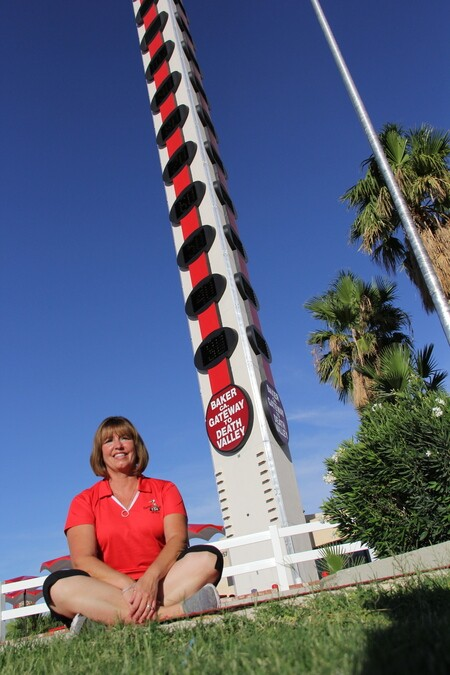 LaRae Harguess at the base of the The World's Tallest Thermometer in Baker CA