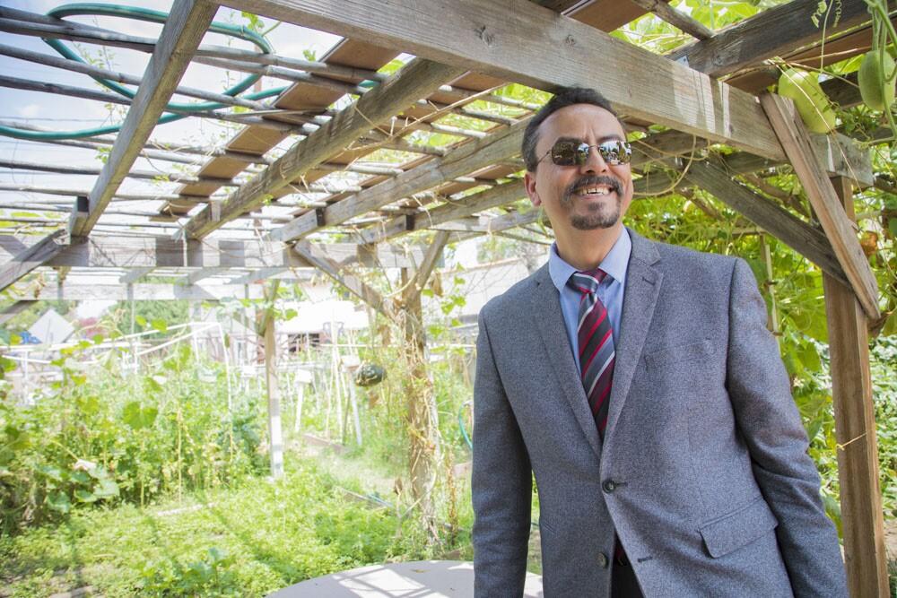 David De La Torre standing at Jardin del Rio community garden.