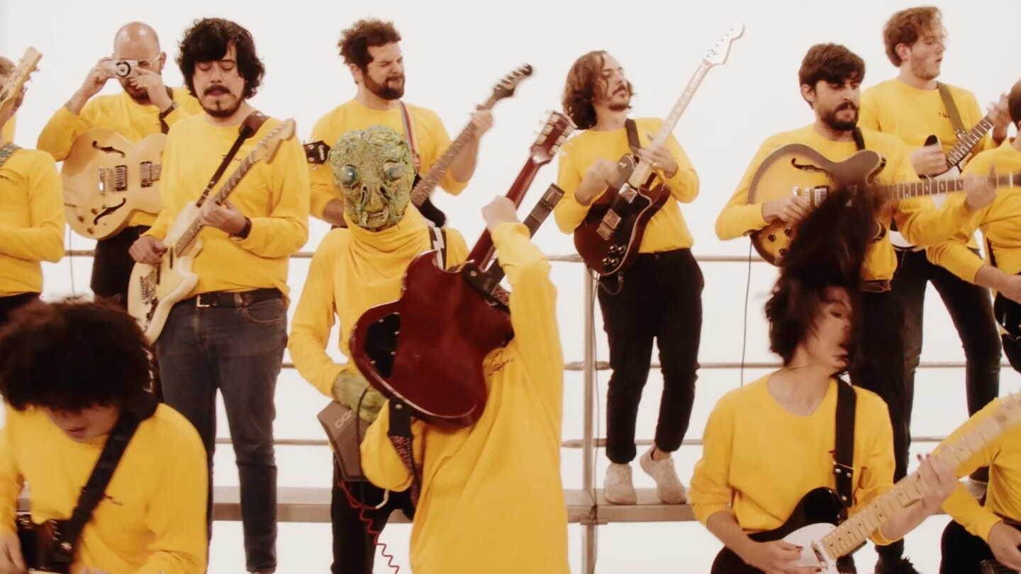 Still from TQM: Several guitarists in jeans and long-sleeved yellow shirts. One has an alien head. One is taking a photo.