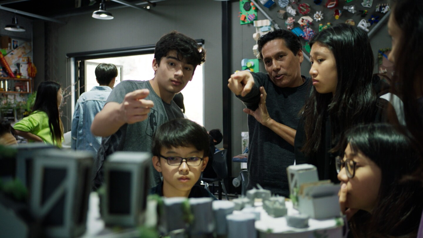 A teacher and his class talk about a model they're building inside a creative classroom.