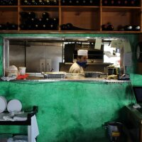 A cook in a mask stands in the kitchen of Cantalini's restaurant in Playa del Rey. | Karen Foshay