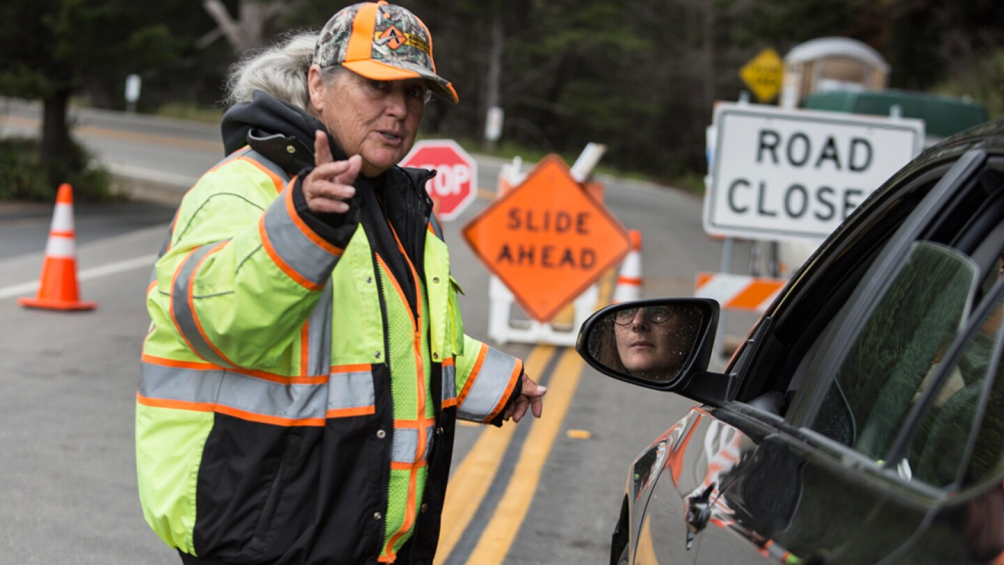 Caltrans contractor Arleen Guzzie gives directions at the Ragged Point road closure. |  Photo: Brian van der Brug/Getty Images