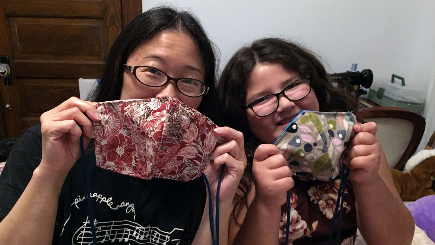 Two Auntie Sewing Squad members, Davine and Gayle Isa, pose with their handmade masks. | Courtesy of Auntie Sewing Squad