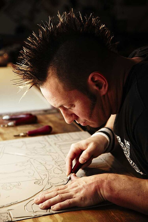 Dave Lefner carving details out of design on linoleum; Photograph by Prakash Shroff   Courtesy of the artist