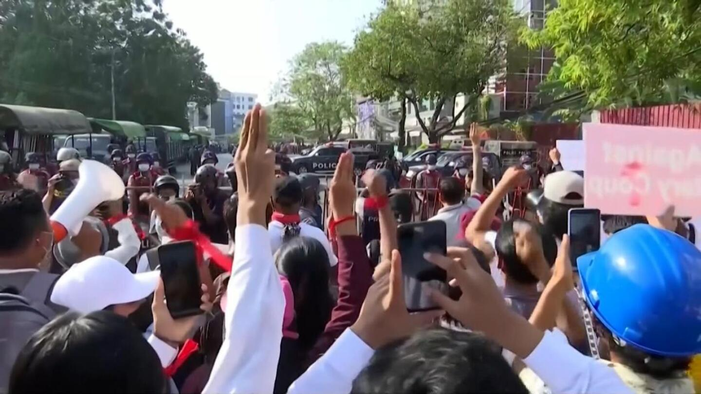 A group of protesters gather as they hold up their phones.