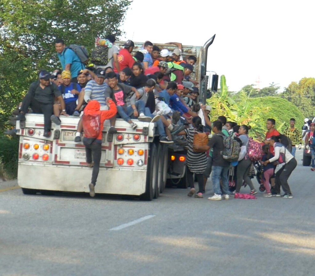 Dozens of migrants hopping onto the back of a truck. | Still from Global Mosaic
