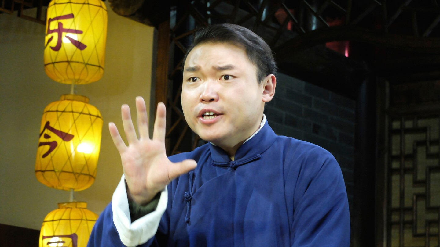 """A Chinese man gestures while mid-speech.   """"The Story of China with Michael Wood: Ancestors"""""""