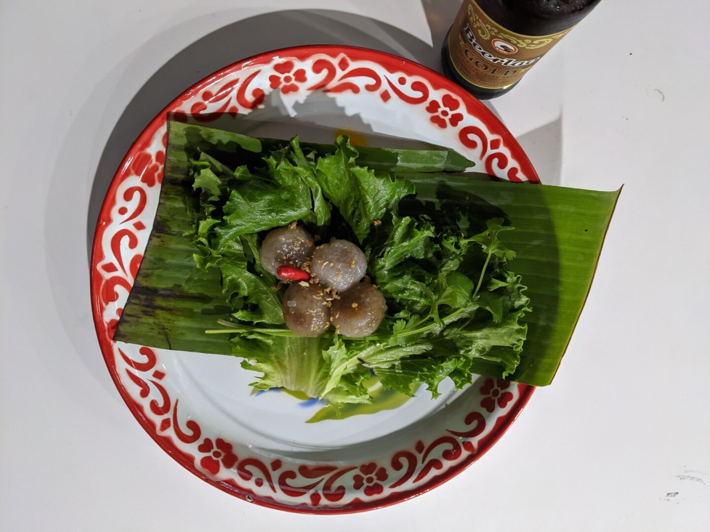 A plate of sakoo yat sai, tapioca dumplings filled with a savory filling and served with fresh vegetables. The dumplings are a light brown color and in the shape of four balls in the center of the plate. They sit on a bed of green lettuce and herbs.