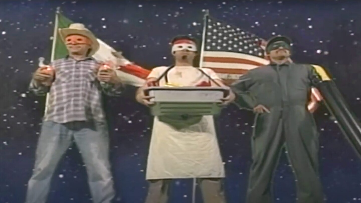 """Essential workers including a farm worker, cook and gardener pose wearing superhero masks in front of a Mexican and and American flag. 