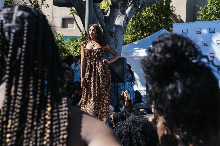 A woman in a leopard print dress poses in front of a crowd