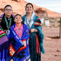 Three Native Amerian Navajo sisters in traditional clothing pose in Monument Valley, Arizona.