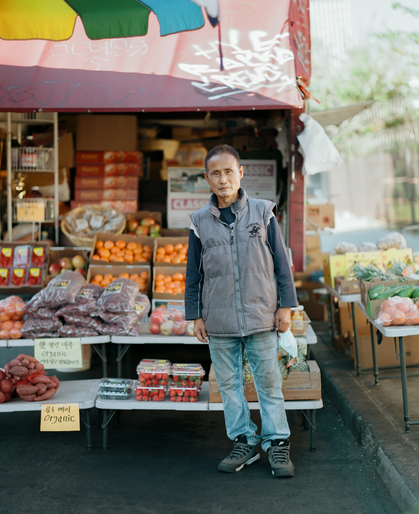 A Koreatown fruit truck vendor stands in front of his product.