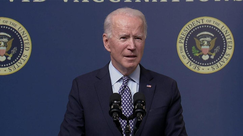 President Joe Biden stands behind two microphones.
