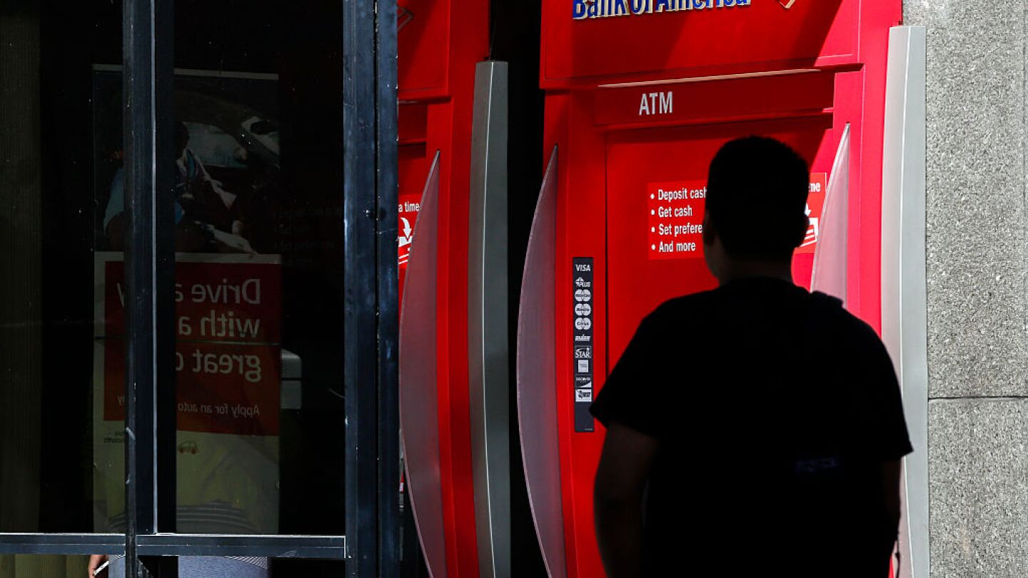 A man walks near a Bank of America Corp. ATM in Los Angeles, California, U.S., on Monday, July 13, 2015.
