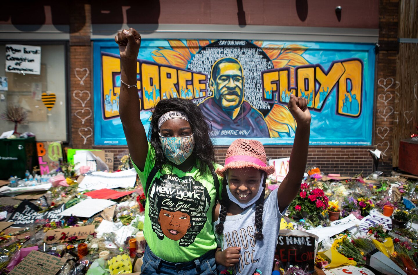 Two girls with fist raised pay their respects at the makeshift memorial for George Floyd