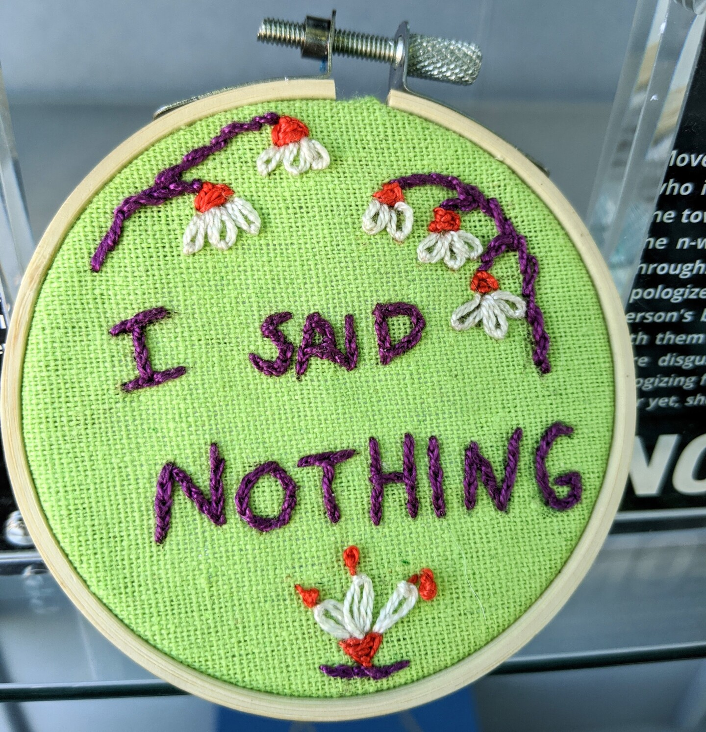 """A small embroidery hoop with bright green fabric stretched across embroidered with the words, """"I said nothing"""" in purple thread. Surrounding it are floral designs featuring white petals, orange details and purple branches."""