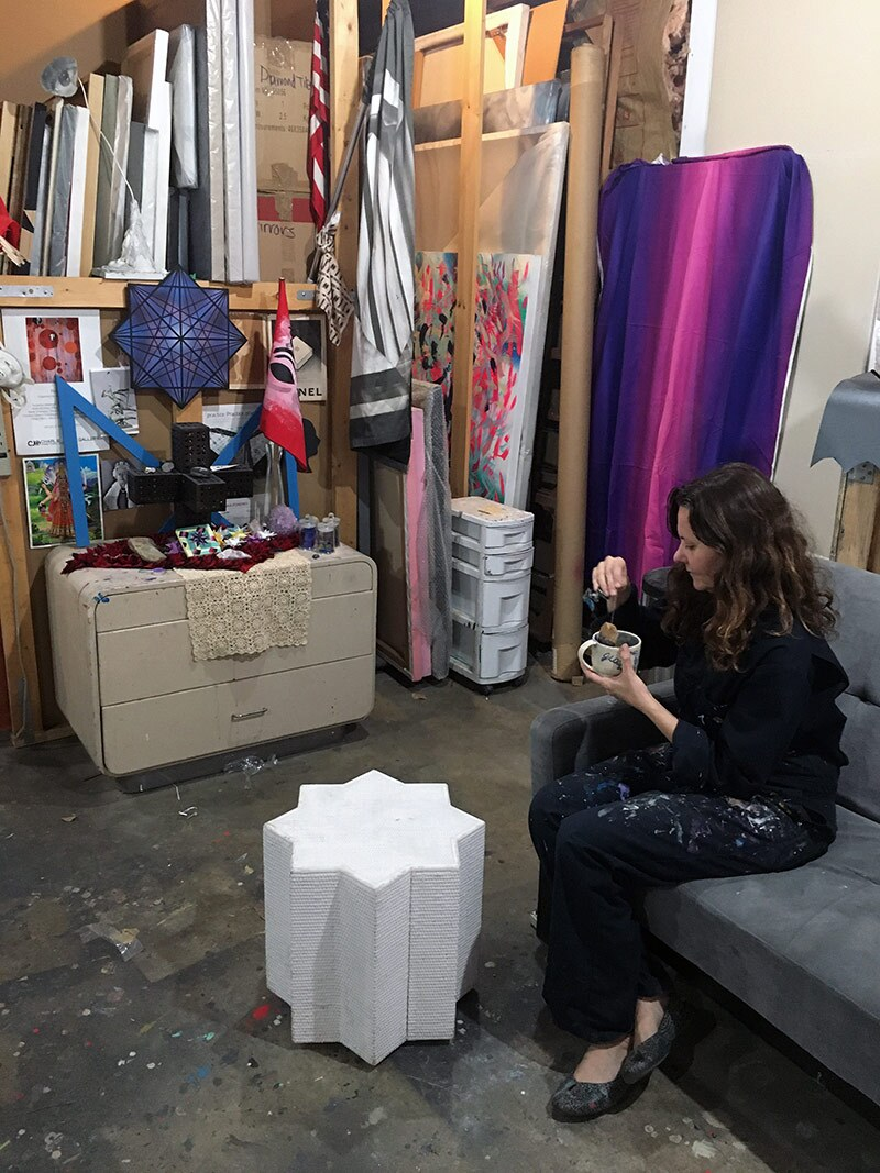 Mary Anna Pomonis drinks tea in front of her studio altar, 2020. | Courtesy of the artist. Photo: Justin Stadel.