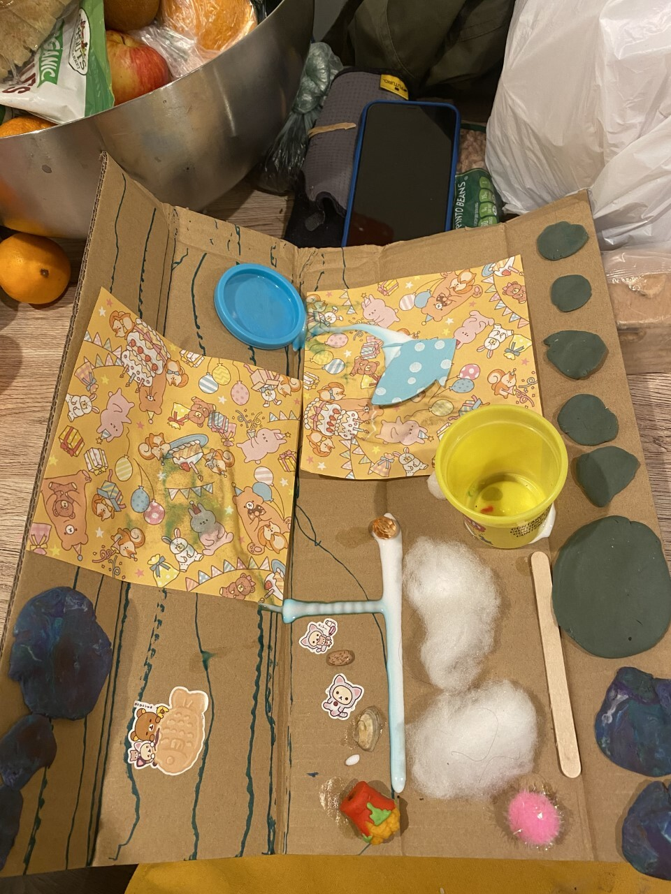 A piece of cardboard with everyday items like cotton, glue and Play-Doh.