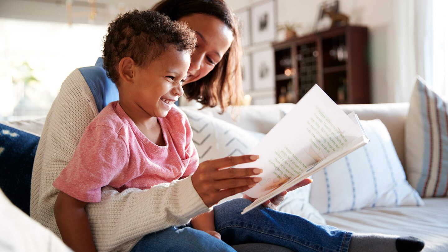 A woman and a little boy read together on a couch