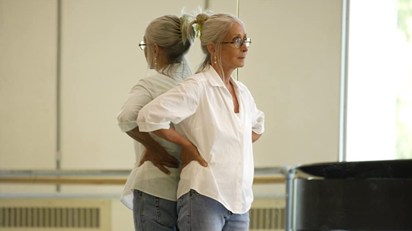 Twyla Tharp standing with her hands on her hips.