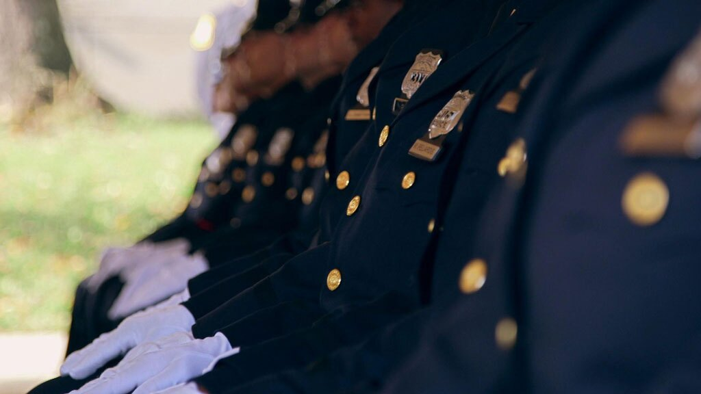 """A line of seated policemen's uniforms. 