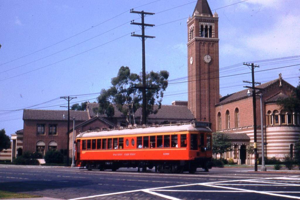 A Santa Monica Air Line car travels eastbound on Exposition Boulevard in front of USC's Mudd Hall. Photo by Alan Weeks, courtesy of the Metro Transportation Library and Archive.